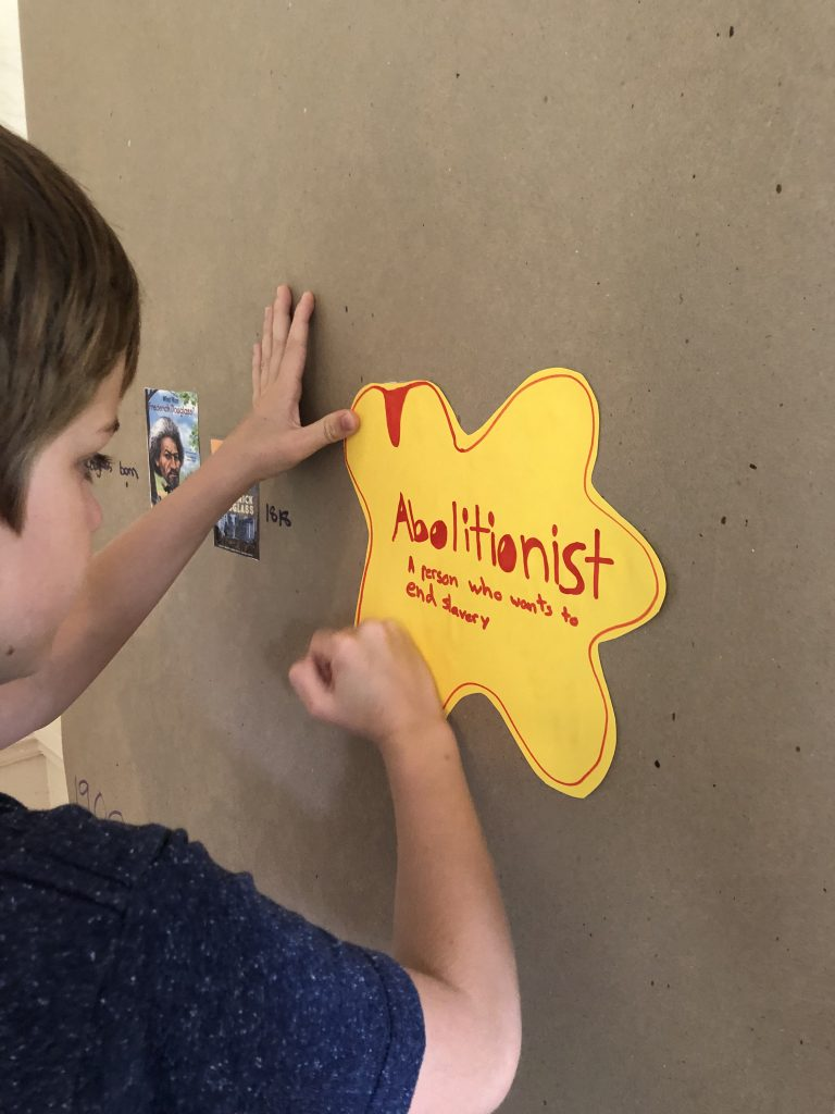 Child posting sign on DIY Black History mural defining abolitionist